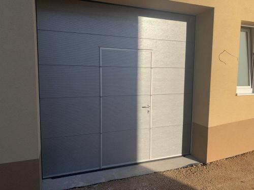 Industrijska vrata Protrend, srebrna, mikroprofilirana z osebnim prehodom z nizkim pragom